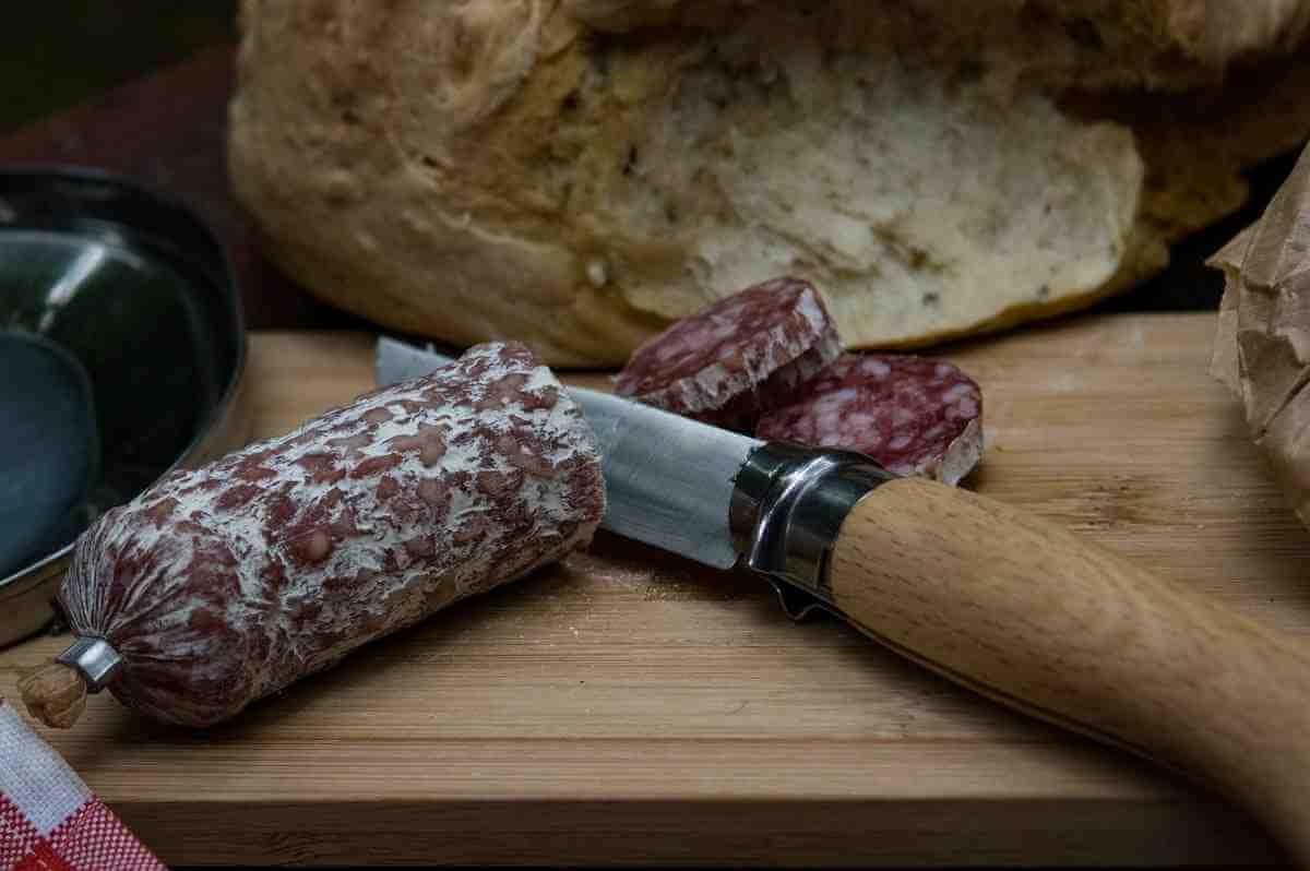 Salami och bröd på skärbräda - italiensk mat